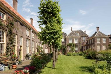 Hollandse hofjes en Vlaamse godshuizen, verborgen caritatieve woonlandschappen